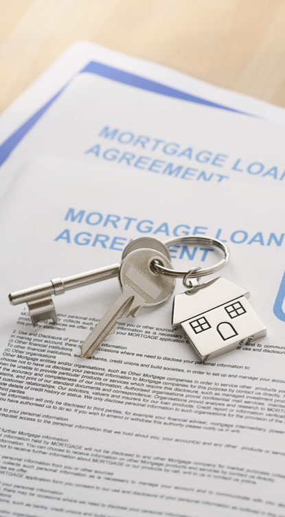 picture of house keys sitting on a mortgage loan agreement